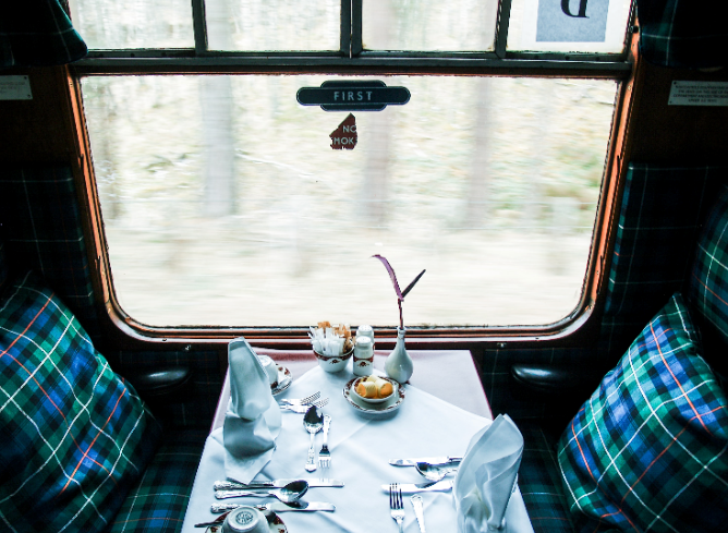 view of two tartan dining train seats, dining table set next to window