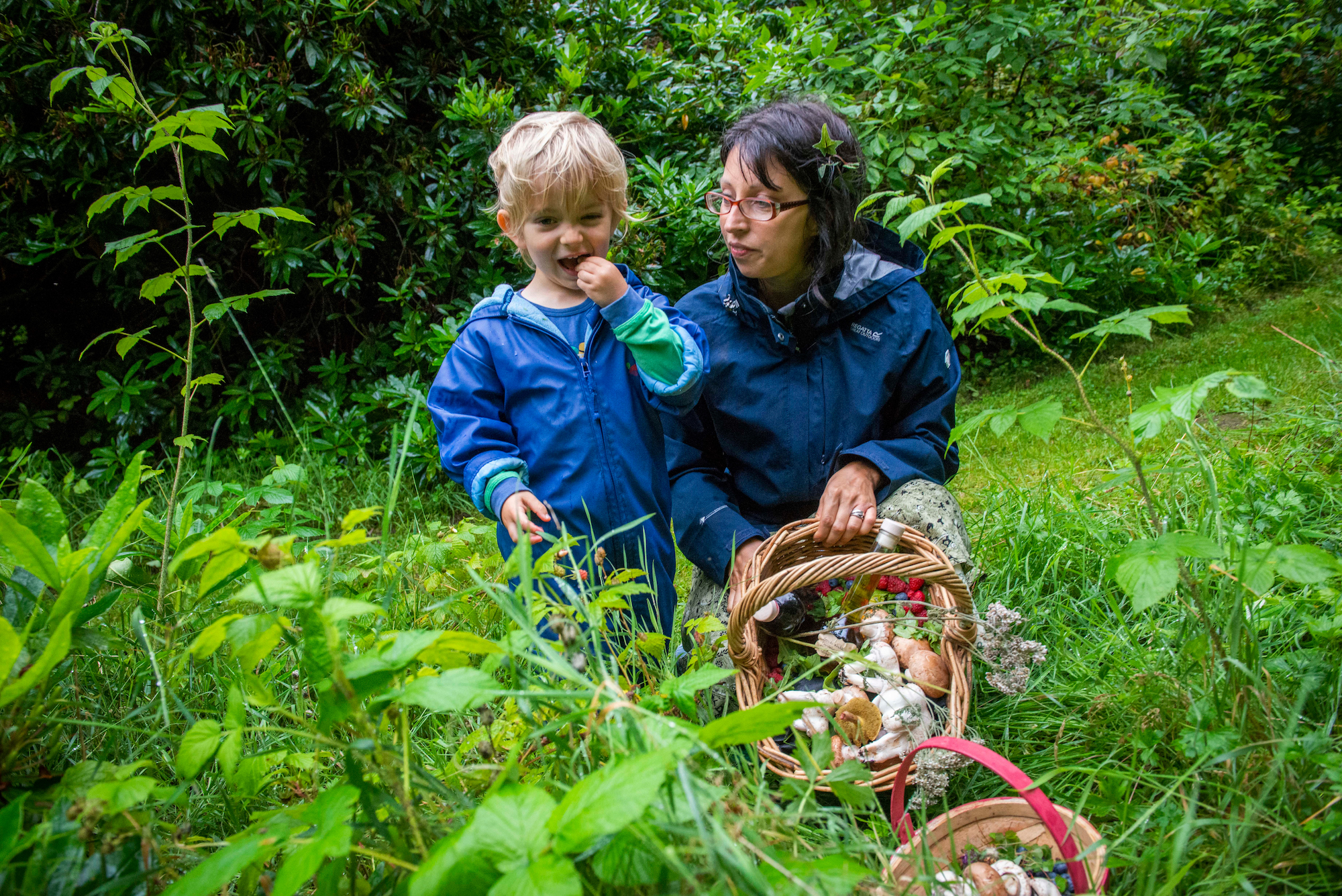 woman and boy foraging in woods