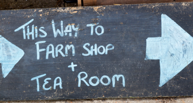 Chalkboard sign 'This way to farm shop and tea room'