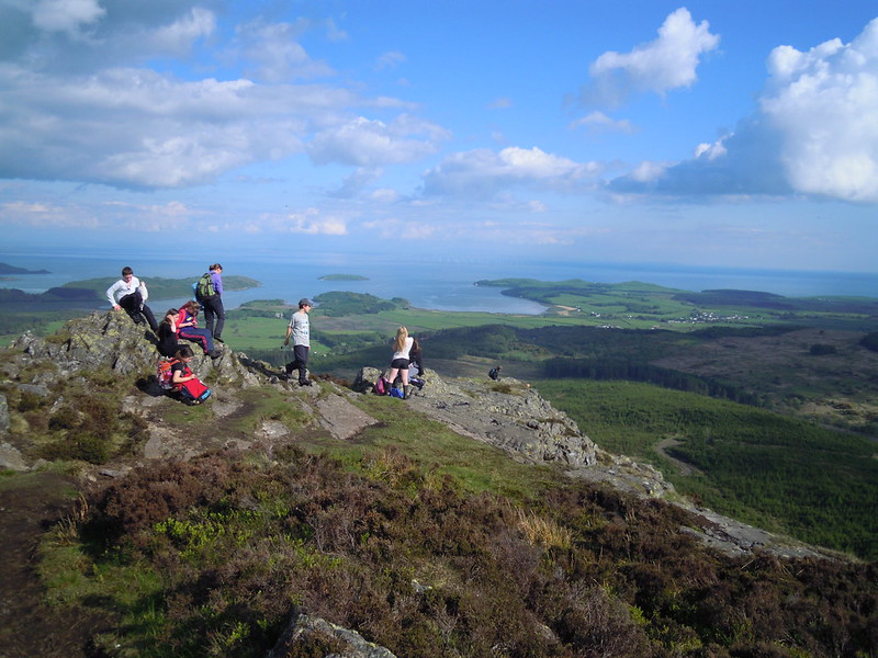 Group of teenagers on hill summit with field and sea views