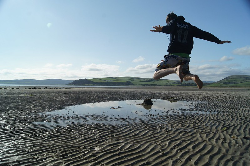 Boy jumping over seawater pool on beach
