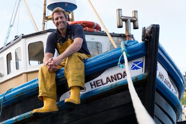 Fisherman sitting on side of boat