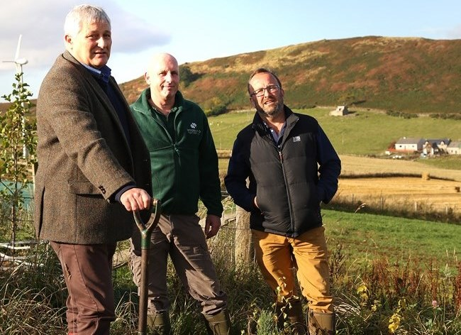 John Finnie MSP planting a Scots pine tree at Ian Mhor, near Dingwall with Willie Beattie from the Woodland Trust Scotland and crofter Jo Hunt.