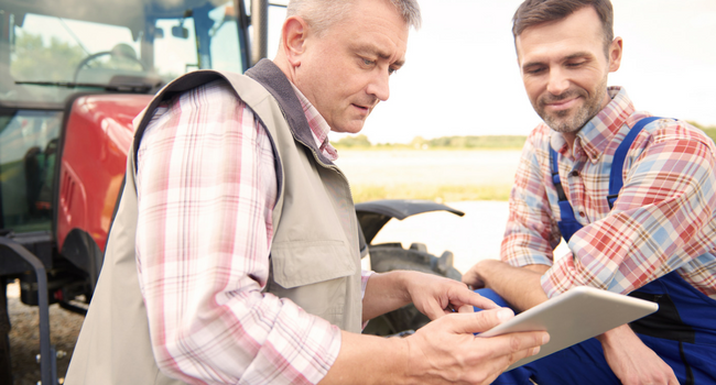 two farmers looking at a tablet beside a tractor