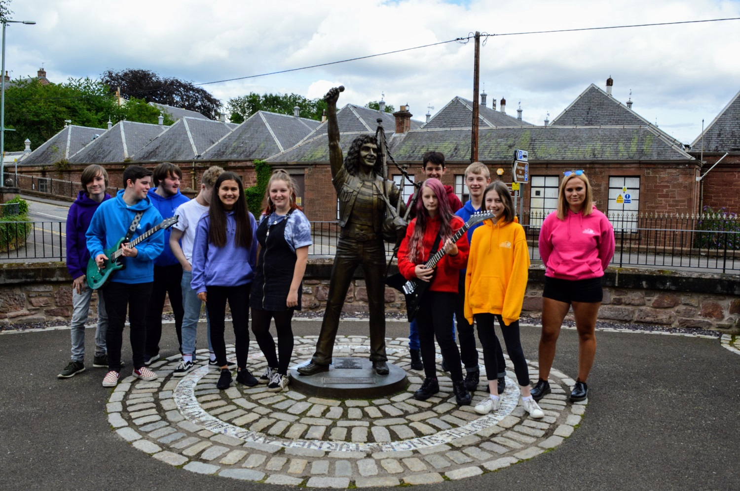Young musicians from the DD8 project stand beside Kirriemuir Bon Scott statue