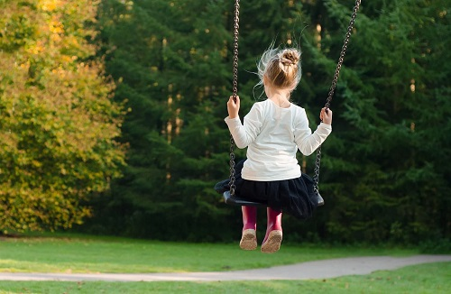 Girl on swing with autumn trees