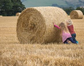 Two small children trying to push large hay bale