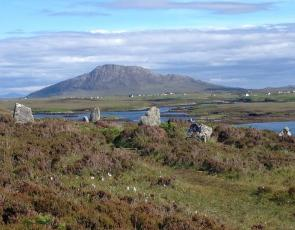 Standing stones on hill overlooking loch and mountain
