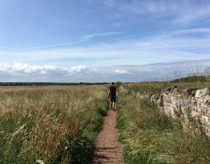Man walking along a path in open countryside with blue skies.