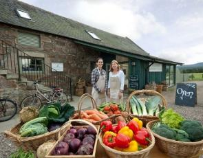 Two women outside Finzean farm shop with boxes of produce