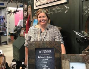 Woman in shop with framed award certificate