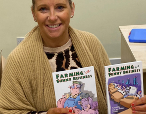 """RSABI Office and Volunteer Manager Lorraine Caven holding copies of """"Farming is Still a Funny Business"""" and its predecessor """"Farming is a Funny Business""""."""