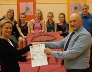 Tom Davis, Chair of the Inner Moray Firth North LEADER Local Area Partnership, presents award to Claire Bath, Chair of Fryish Gymnastics Club with Senior Coach Sonny Rhind and some of the young gymnasts looking on.