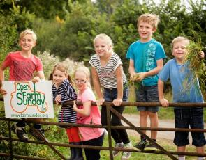 Children leaning on gate with Open Farm Sunday sign