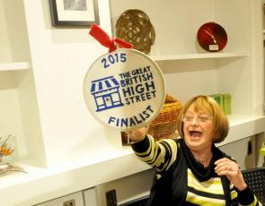 Woman holding up Great British high Street award
