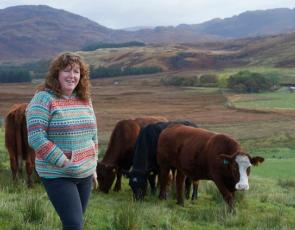 Crofter Fiona MacDonald with cows and hills in the background