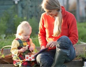Woman and child having picnic in allotment