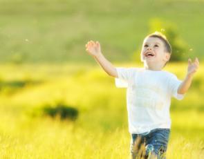 Boy chasing bubbles in field