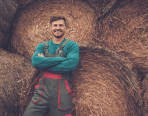 young farmer leaning against bales