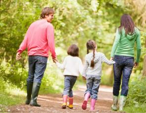 Family walking on path in wood