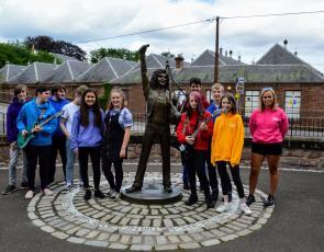 Young musicians from the DD8 project stand beside Kirriemuir Bon Scott statue