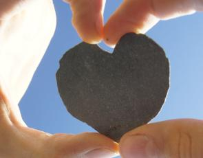 Small heart-shaped stone held between hands