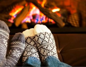 Two people warming their feet by a fire