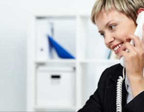 woman at desk using phone