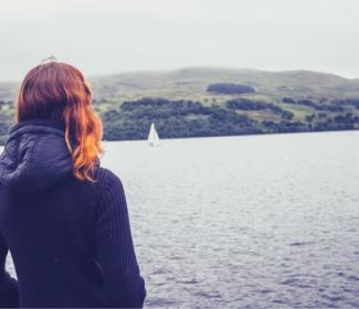 Woman standing at side of loch