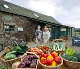 Two women outside Finzean farm shop with boxes of produce