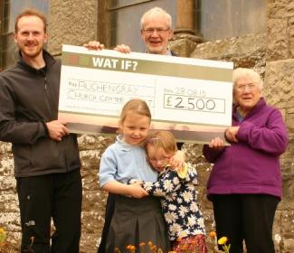 People holding a giant cheque outside a church