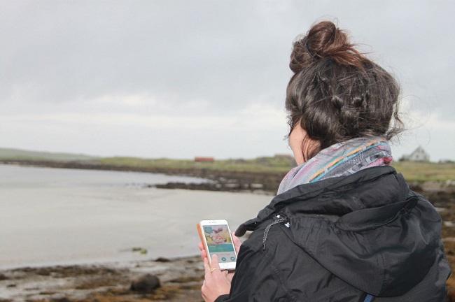 Woman using app on phone beside water
