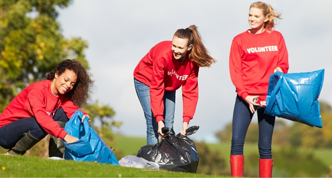 Three women picking up litter