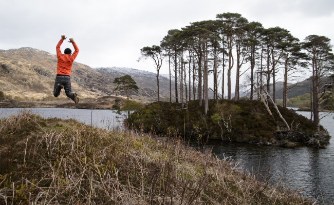Person jumping at side of loch