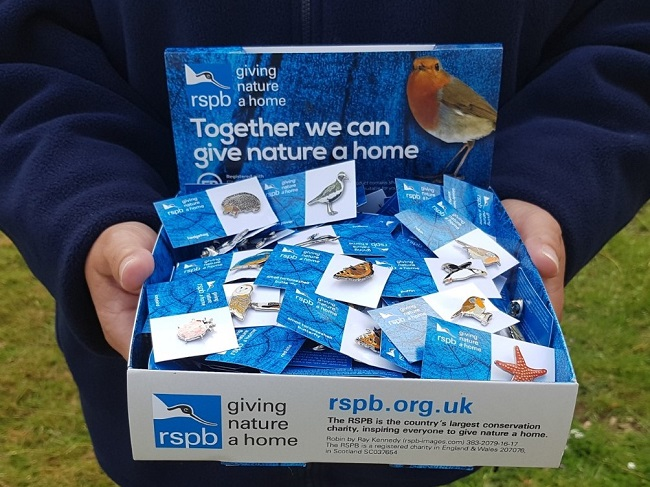 Person holding RSPB collection box with pins