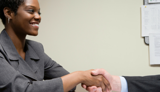 woman smiling and shaking hands with interviewer
