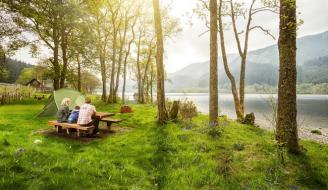 People sitting next on picnic bench next to loch