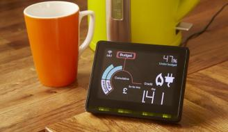 Photo with smart meter, mug and kettle on kitchen table