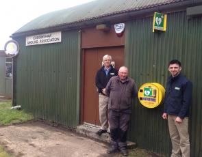 Picture of a WAT IF? trustee and a Muirhall Energy representative outside an Angling club which has a defibrillator on wall