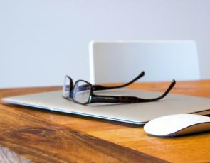 glasses and laptop on a desk