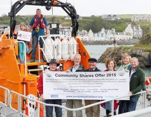 People in lifeboat in harbour with community shares banner