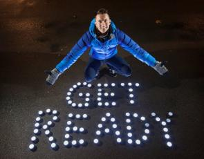 Sean Batty with 'Get Ready' written on ground with torches
