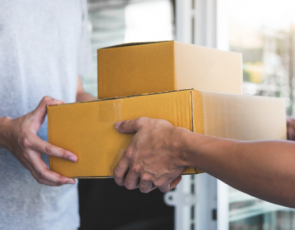 Man handing two parcels to other man