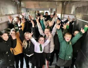 Children on farm visit with hands in air
