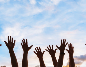 People with hands in the air against blue sky