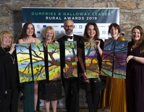 The winners holding their 7 piece work of textile art from artist Jo Gallant. Photo credit: Mike Bolam