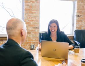 woman sitting across desk from man