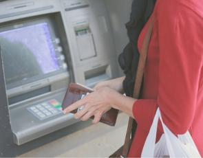 young woman using cash machine
