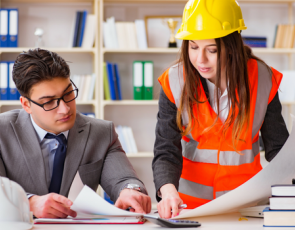 Woman with hard hat speaking to man at desk