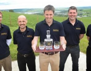 Picture of 5 men holding a whisky decanter and glasses with distilery name engraved on the glassware